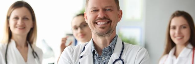 Riuscito medico sorridente dell'uomo che sta contro il fondo dei colleghi in clinica