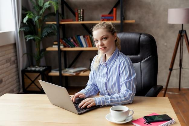 Riuscita giovane imprenditrice sorridente utilizzando laptop e computer in ufficio. foto di alta qualità
