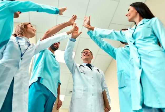 Il team di medici di successo si è messo in cerchio e si è dato cinque a vicenda come segno di un'operazione riuscita e di una vittoria.