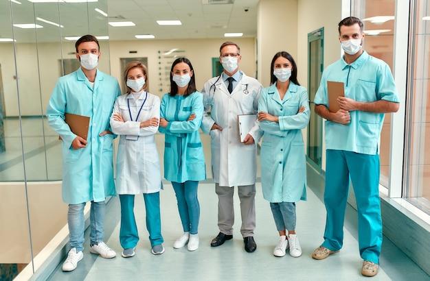 Un team di medici di successo che indossano maschere mediche protettive si trova nel corridoio della clinica. protezione in quarantena e covid-19.