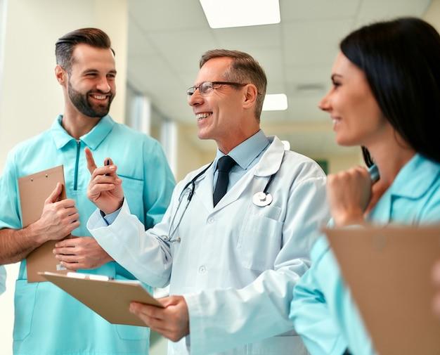 Un team di medici di successo con cartelle cliniche che discutono di trattamenti stando in piedi nel corridoio della clinica. un anziano medico insegna ai giovani stagisti.