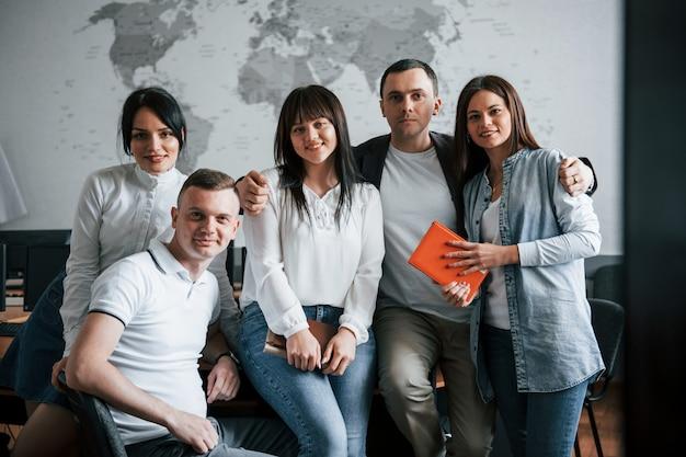 Squadra di successo di giovani liberi professionisti che posano per la fotografia dopo il lavoro