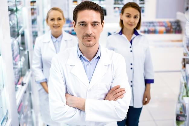 Tre farmacisti di successo in piedi uomo davanti due donne da dietro