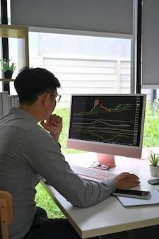 Commerciante di successo che lavora con grafici e rapporti di mercato sullo schermo del computer in un ufficio moderno.