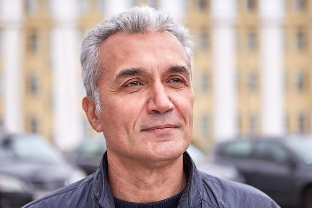 Un uomo ben curato di successo di oltre 50 anni, i capelli grigi corti sembrano vestiti casual