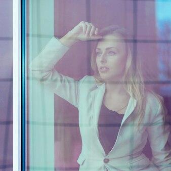 Una donna leader di successo guarda fuori dalla finestra della sua stanza personale