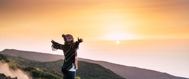 La donna di successo in cima al mondo apre le braccia e abbraccia un bellissimo tramonto colorato di fronte a lei