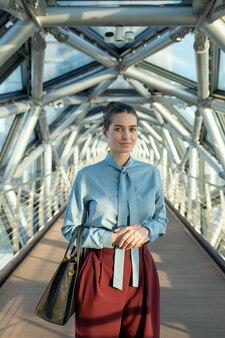 Giovane donna bruna di successo delegata o segretaria in abbigliamento casual intelligente in piedi nel corridoio all'interno del business center contemporaneo
