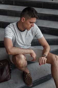 Il giovane uomo d'affari di successo in pantaloncini alla moda in scarpe marroni scamosciate in una maglietta a righe con una borsa in pelle guarda l'orologio