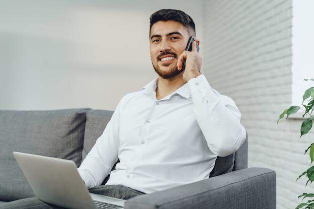 Riuscito giovane imprenditore parlando sul suo cellulare, ritratto