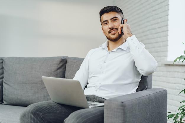 Riuscito giovane uomo d'affari che parla sul suo cellulare