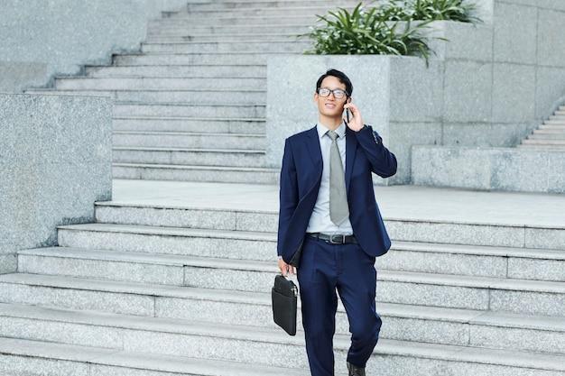 Riuscito giovane uomo d'affari con valigetta camminando per strada e parlando al telefono