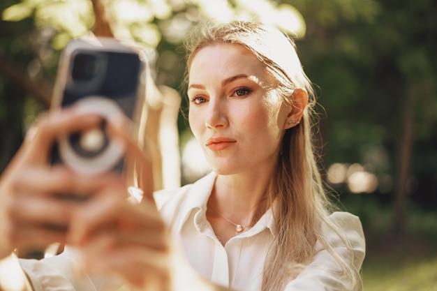 Giovane imprenditrice di successo seduta in un caffè all'aperto e utilizza lo smartphone