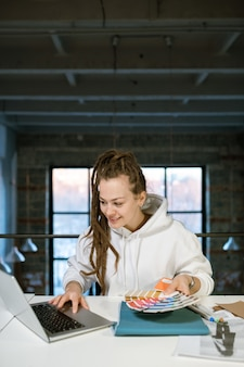 Giovane designer creativo di successo con tavolozza dei colori seduto davanti al computer portatile mentre lavora alla nuova collezione di moda