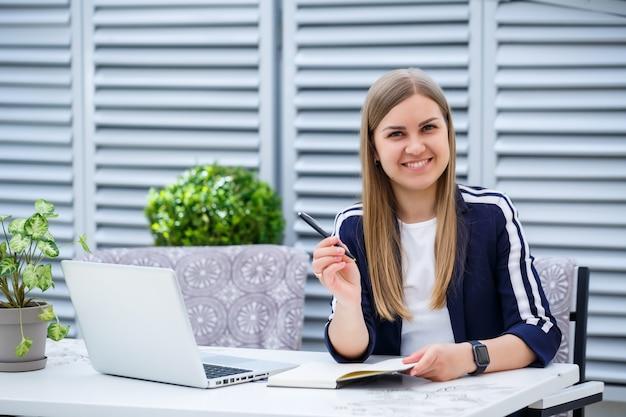 Manager di successo giovane donna d'affari seduto a un tavolo con un laptop e un blocco note che lavora su un nuovo progetto di sviluppo, una studentessa scrive un rapporto sul suo computer
