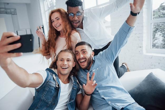 Che bella foto. giovani amici allegri che prendono i selfies sul sofà e sull'interno bianco