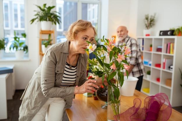 Un tale piacere. gioiosa donna anziana protesa in avanti mentre annusa i fiori nel vaso
