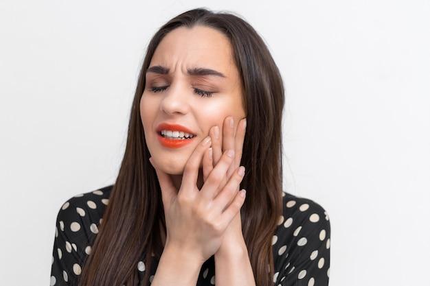 Soffre di mal di denti. bella giovane donna che soffre di mal di denti, in piedi su sfondo bianco. concetto di cure odontoiatriche. emozioni della gente.