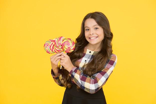 Dipendenza da zucchero. bambino felice con caramelle dolci. bambino del bambino che tiene il fondo giallo della caramella delle lecca-lecca. dieta di rottura. bambino felice con la caramella. alimentazione scolastica. calorie ed energia. pazzi per i dolci.