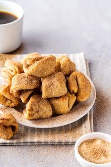 Biscotti di zucchero su un piatto, tazza da caffè, sfondo grigio, formato verticale.