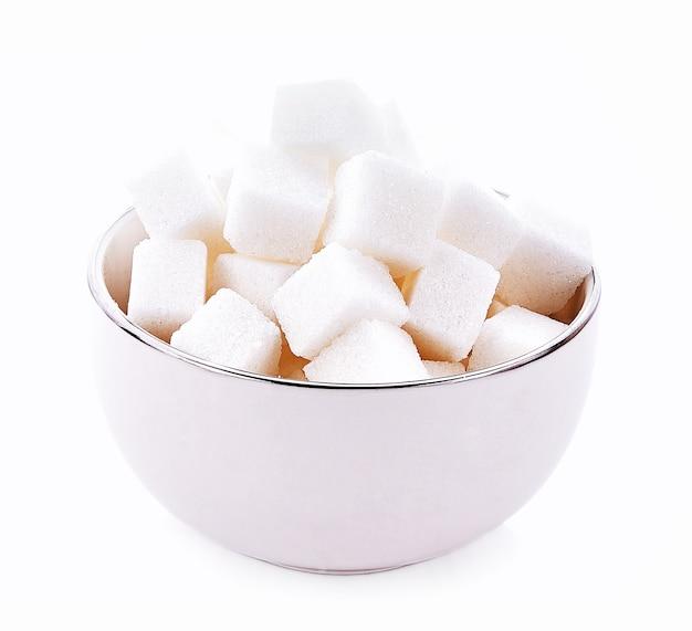 Zolletta di zucchero in ciotola su sfondo bianco