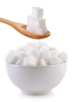 Zolletta di zucchero nella ciotola e nel cucchiaio di legno isolati
