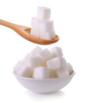 Zolletta di zucchero nel cucchiaio e nella ciotola isolati
