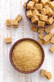 Zollette di zucchero in una ciotola sul tavolo di legno