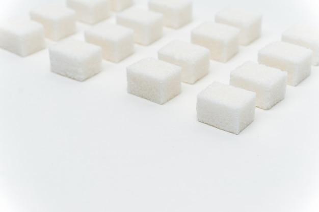 Cubetti di zucchero a parete chiara per ingredienti dolci distribuiti uniformemente.
