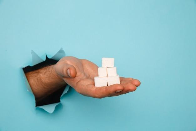 Zollette di zucchero in mano da un buco strappato in carta blu