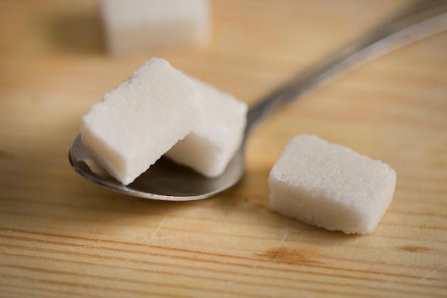 Cubetti di zucchero e un cucchiaio sul tavolo