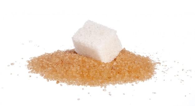 Zollette di zucchero e zucchero di sabbia su un bianco