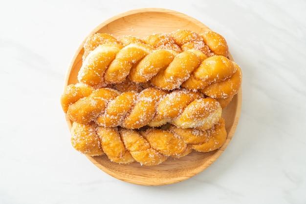 Ciambella di zucchero a forma di spirale su piatto di legno