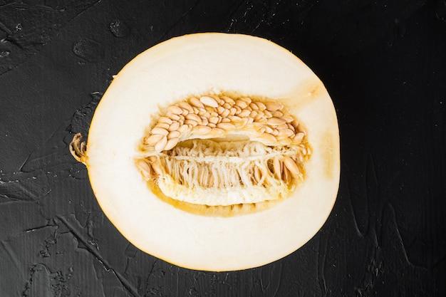 Melone di zucchero tagliato a metà set, su sfondo nero tavolo in pietra scura, vista dall'alto piatta