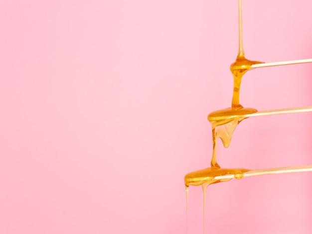 La pasta di zucchero per la depilazione scorre su una spatola di legno