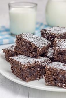 Brownies fatti in casa con zucchero a velo e un bicchiere di latte