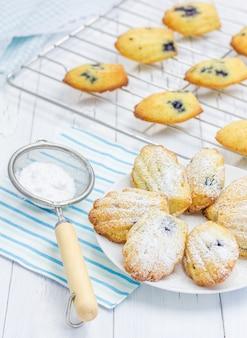 Madeleine fatte in casa con zucchero a velo e mirtilli