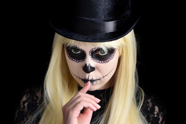Ragazza del cranio dello zucchero con bionda in cappello nero, colpo dello studio. copia spazio.