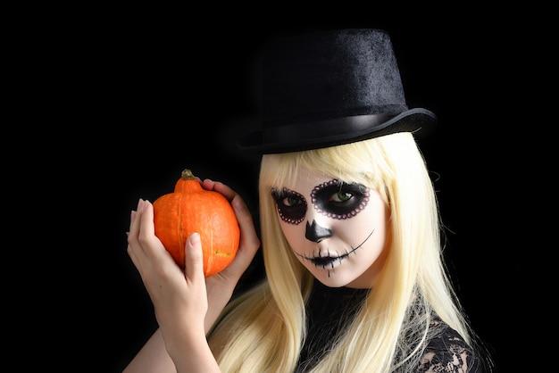 Ragazza del cranio dello zucchero con bionda in cappello nero con la zucca, colpo dello studio. copia spazio.