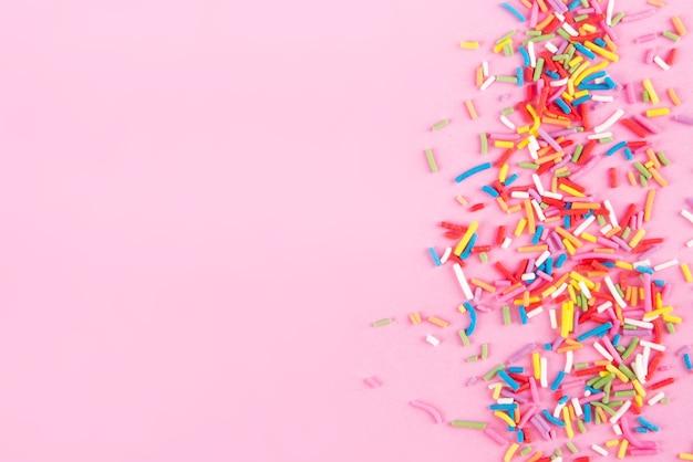 Cuori di puntini cospargere di zucchero, decorazione per torte e prodotti da forno, come sfondo. isolato sul rosa.