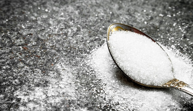 Zucchero in un cucchiaino. su fondo rustico.