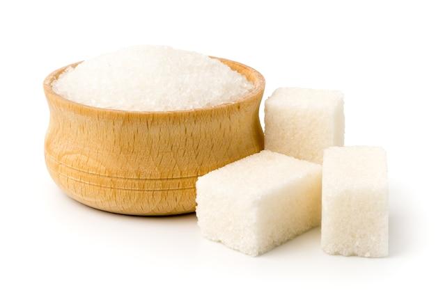 Zucchero in zolla di legno e cubetti raffinati sulla superficie bianca, primo piano