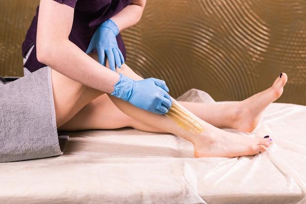 Sugaring epilazione skin care con zucchero liquido al primo piano gambe.