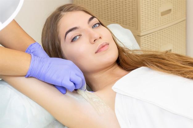 Sugaring: epilazione con zucchero liquido sotto l'ascella. master of sugaring rendendo la procedura di depilazione per donna. epilazione con pasta di zucchero liquate.