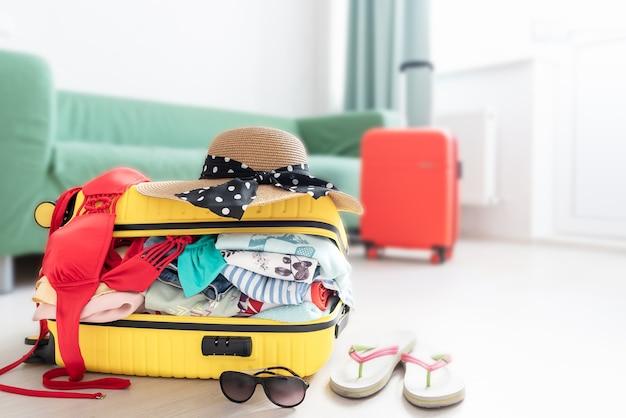 Valigia imballata per le vacanze, aprire i bagagli gialli pieni di vestiti nella stanza