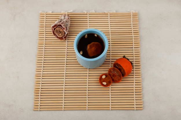 Sujeonggwa- tradizionale tè freddo coreano alla frutta o punch freddo su stuoia di bambù.