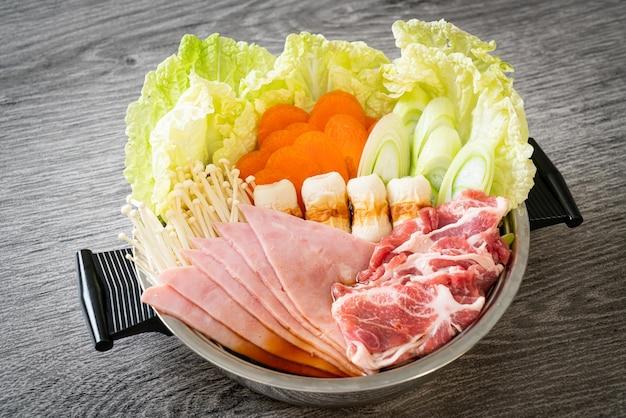 Zuppa nera sukiyaki o shabu con carne cruda e verdure - stile cibo giapponese