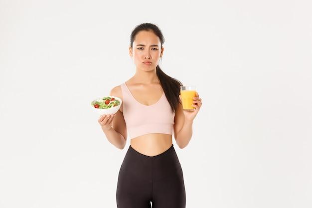 La ragazza asiatica carina imbronciata e riluttante odia mangiare sano, tenere in mano insalata e succo d'arancia con la faccia imbronciata infastidita, odiare essere a dieta e allenarsi.