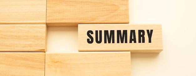 Testo sommario su un listello di legno adagiato su un tavolo bianco