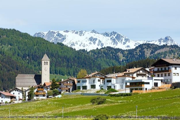Vista del villaggio di montagna alpino estivo con prato erboso (italia)